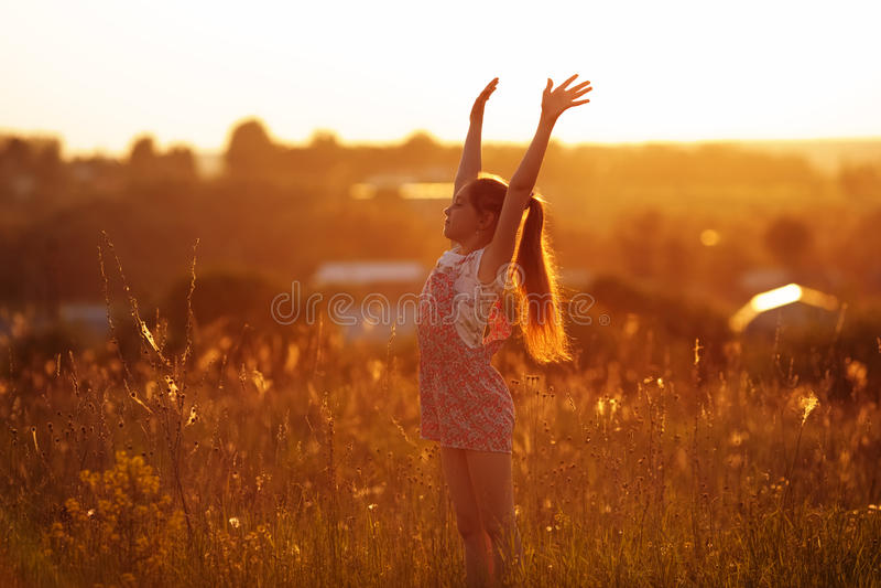 Muchacha feliz en un campo el la tarde del verano imagen de archivo libre de regalías