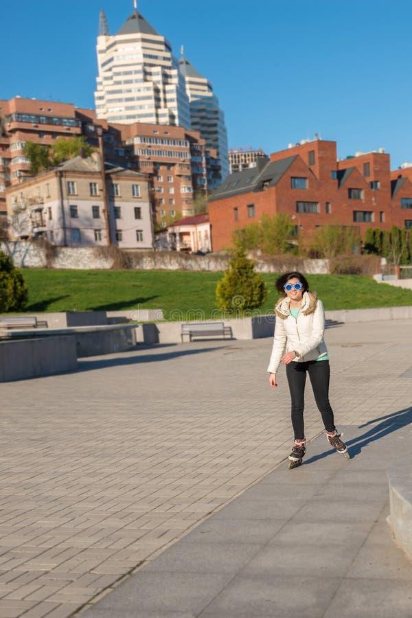 Muchacha feliz en un patinaje sobre ruedas divertido de las gafas de sol en el parque foto de archivo libre de regalías