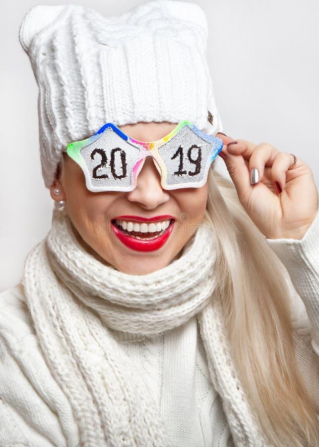 Muchacha feliz en un sombrero y una bufanda blancos, vidrios divertidos que llevan con la inscripción '2019 ' imagen de archivo libre de regalías