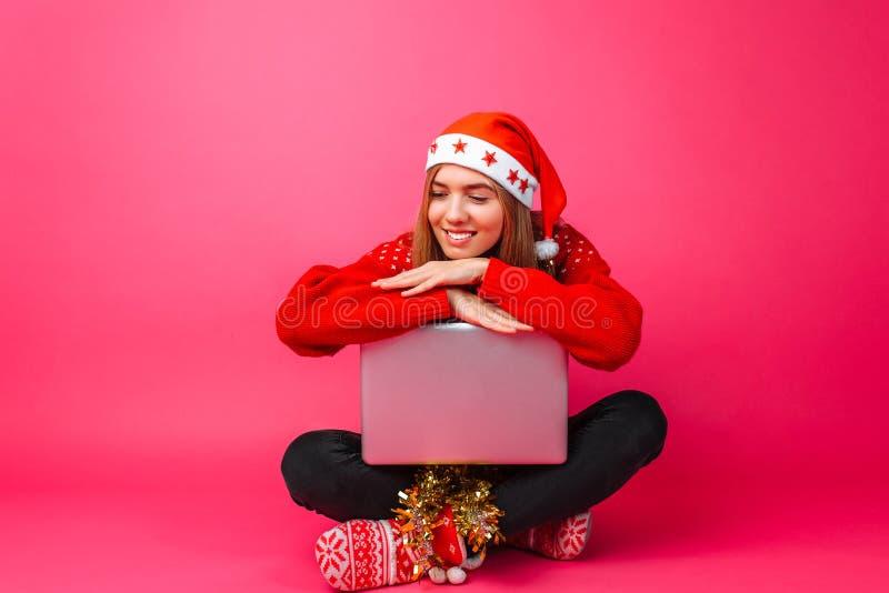 Muchacha feliz en un suéter y un sombrero rojos de Papá Noel, sentándose con un ordenador portátil foto de archivo libre de regalías