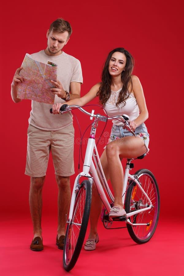 Muchacha feliz en una bicicleta al lado de un individuo con una tarjeta en un fondo rojo imagenes de archivo