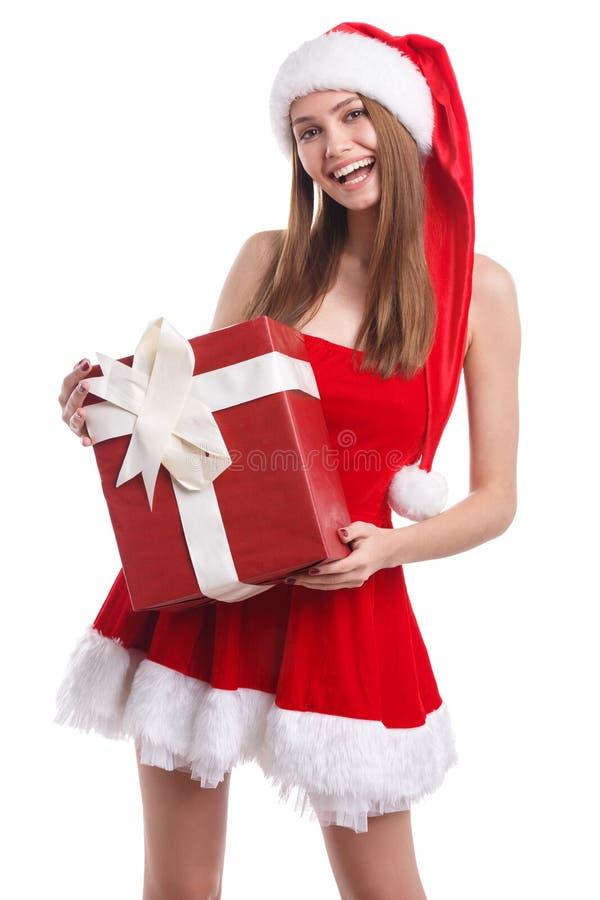 Muchacha feliz en vestido rojo y el sombrero de santa que sostienen una caja de regalo y que sonríen dulce Aislado imagenes de archivo