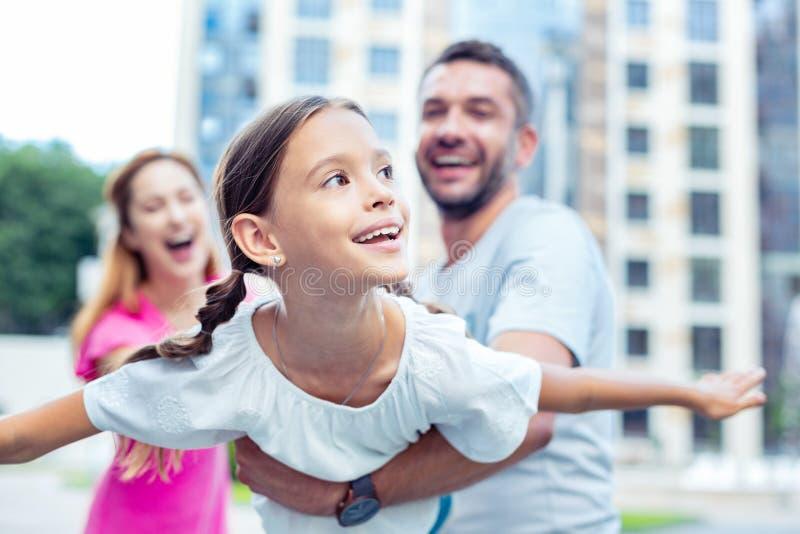 Muchacha feliz encantada que juega con sus padres fotografía de archivo libre de regalías