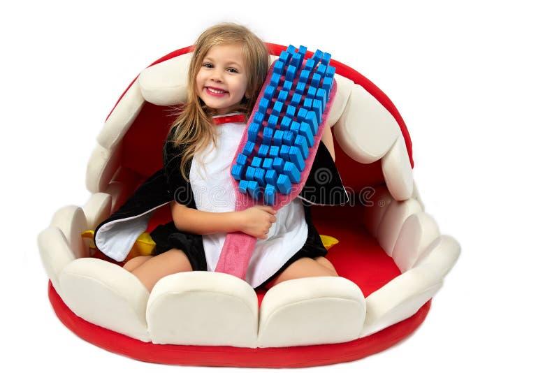 Muchacha feliz encantadora con el cepillo de dientes del juguete fotografía de archivo