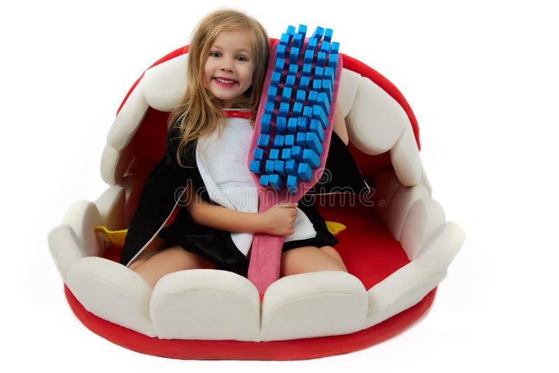 Muchacha feliz encantadora con el cepillo de dientes del juguete imagen de archivo