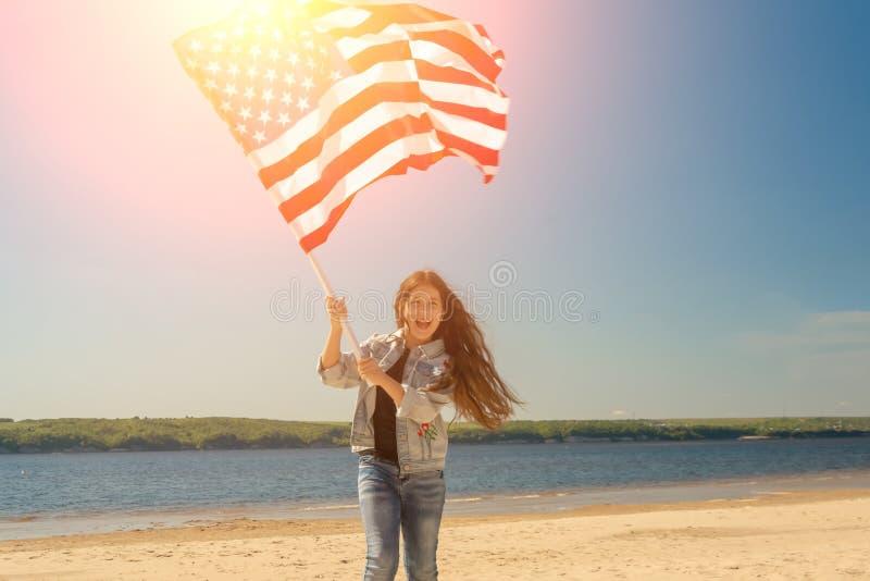 Muchacha feliz hermosa con el pelo largo negro con la bandera americana en un d?a soleado brillante foto de archivo libre de regalías