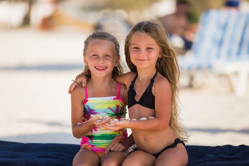 Muchacha feliz hermosa dos con las cáscaras en sus manos fotos de archivo