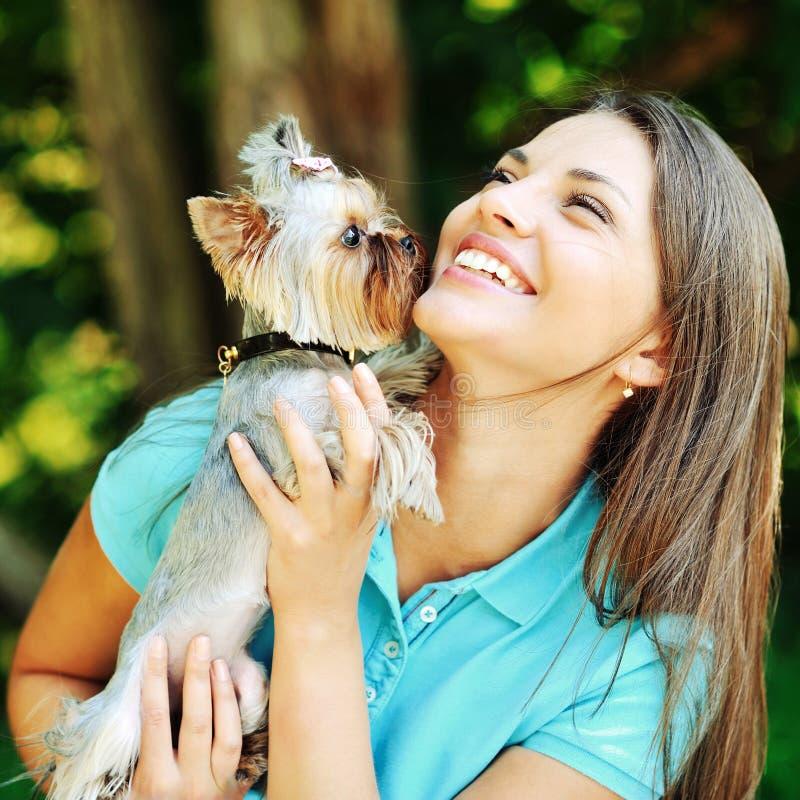 Muchacha feliz hermosa que juega con su pequeño perro y que se divierte fotografía de archivo