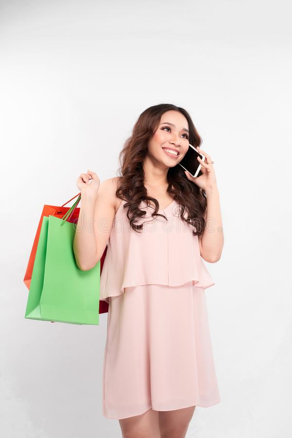 Muchacha feliz imponente con el pelo largo que se coloca con los bolsos que hacen compras coloridos y que habla en el teléfono mó fotos de archivo