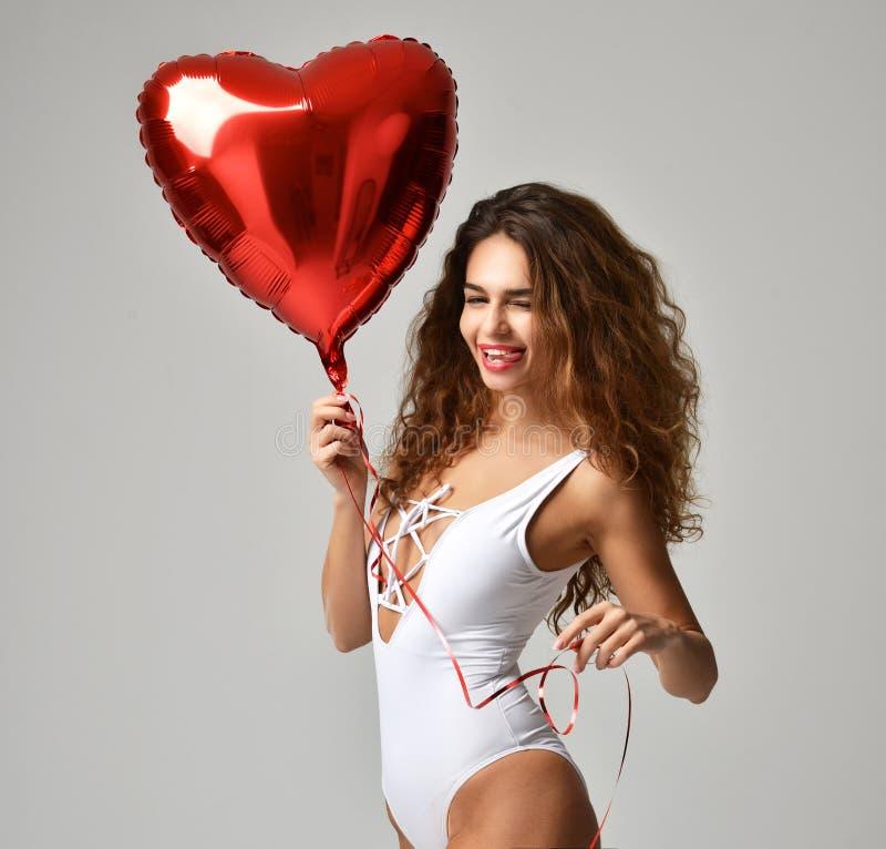 Muchacha feliz joven con el globo rojo del corazón como presente para el birthda imagen de archivo