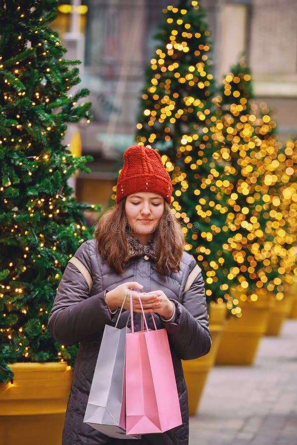 Muchacha feliz joven con los bolsos de compras que camina en la calle, fondo colorido del bokeh de las luces imagenes de archivo
