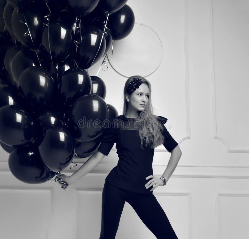 Muchacha feliz joven con los globos negros como presente para el cumpleaños p fotografía de archivo libre de regalías