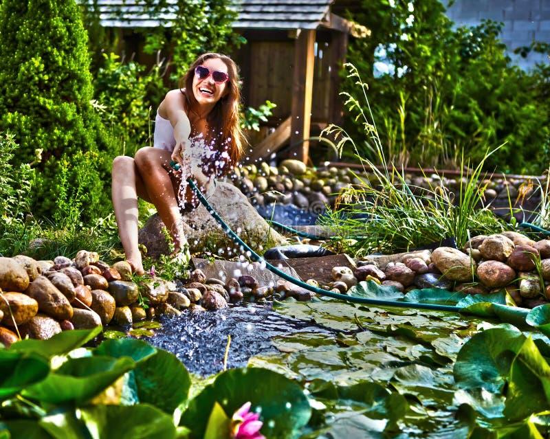 Muchacha feliz joven con streamlet del jardín cerca de la charca imagenes de archivo