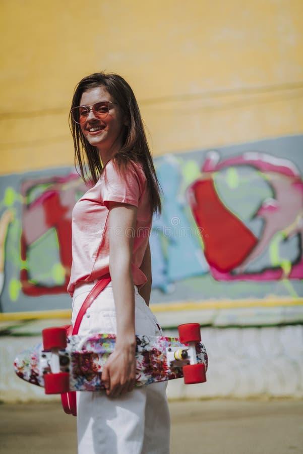 Muchacha feliz joven del inconformista con el tablero del penique imágenes de archivo libres de regalías