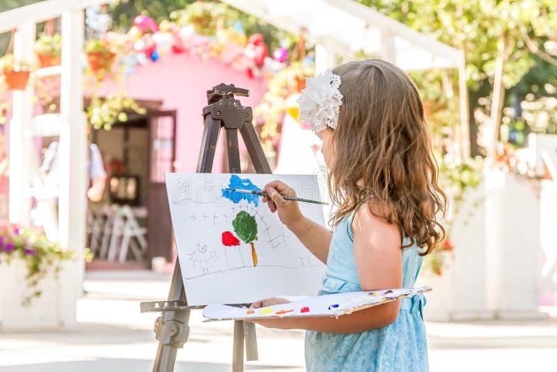 Muchacha feliz joven del niño que dibuja una imagen al aire libre fotos de archivo
