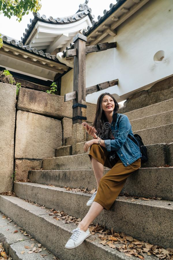 Muchacha feliz joven en hacer excursionismo el onque se sienta de las vacacioneslas escaleras en Japón viajero elegante que es imagen de archivo libre de regalías