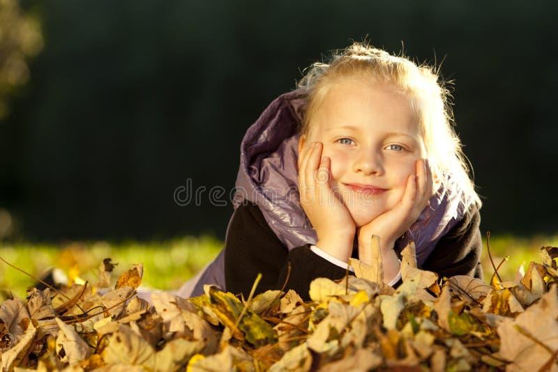 Muchacha feliz joven que miente en suelo en hojas de otoño foto de archivo libre de regalías