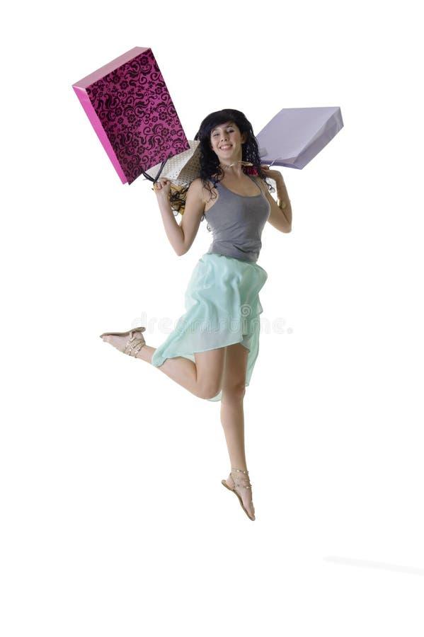 Muchacha feliz joven que salta con sus paquetes de las compras fotografía de archivo libre de regalías