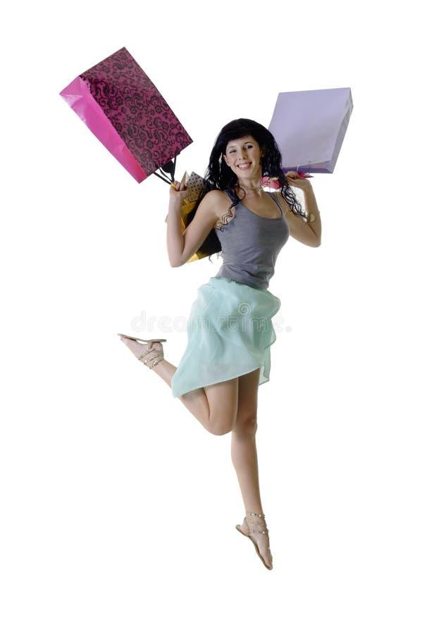 Muchacha feliz joven que salta con sus paquetes de las compras foto de archivo libre de regalías