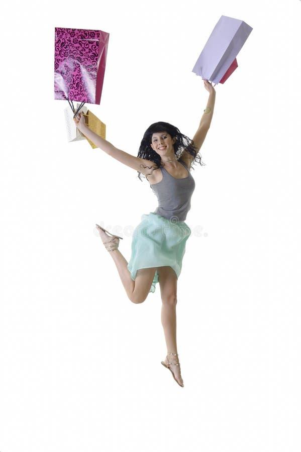 Muchacha feliz joven que salta con sus paquetes de las compras fotos de archivo