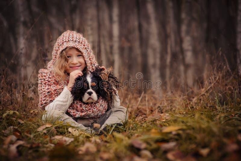 Muchacha feliz linda del niño con su perro en paseo acogedor del otoño en bosque foto de archivo libre de regalías