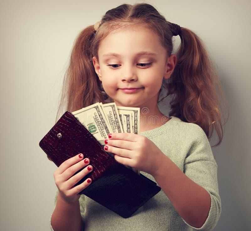 Muchacha feliz linda del niño que sostiene la cartera y que mira en dólares y th imagen de archivo libre de regalías