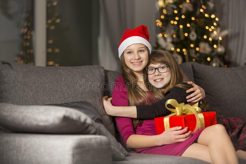 Muchacha feliz que abraza a la hermana en el sofá durante la Navidad imagen de archivo libre de regalías