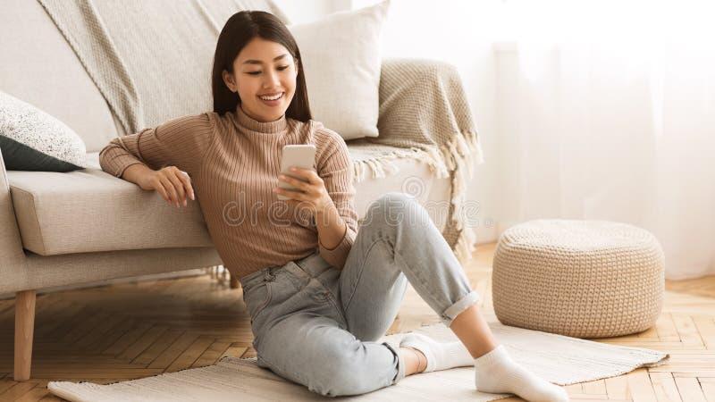 Muchacha feliz que charla en redes sociales en el teléfono en casa foto de archivo libre de regalías