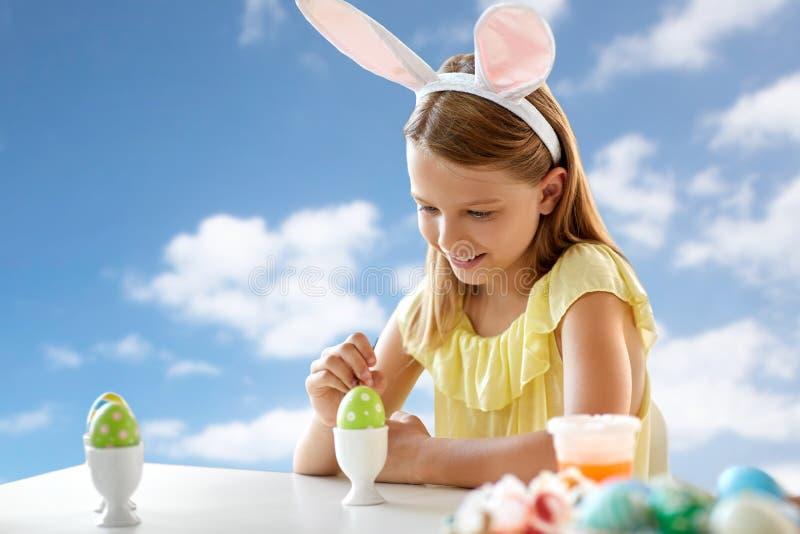 Muchacha feliz que colorea el huevo de Pascua sobre el cielo azul fotografía de archivo