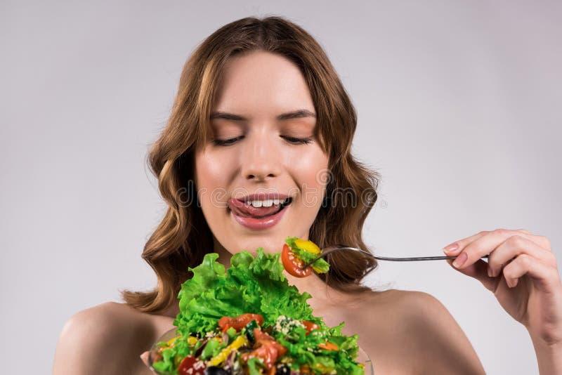 Muchacha feliz que come la ensalada fresca aislada foto de archivo