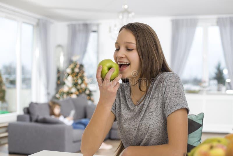 Muchacha feliz que come la manzana en casa imagen de archivo