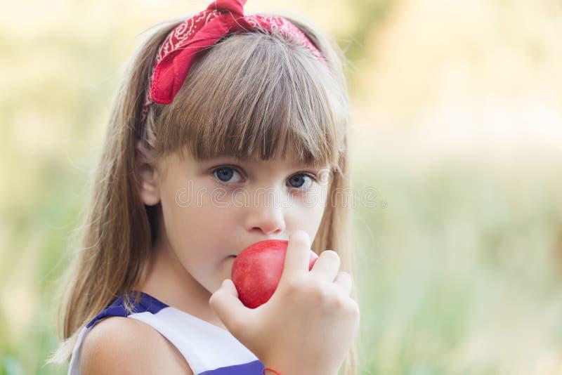 Muchacha feliz que come una manzana foto de archivo