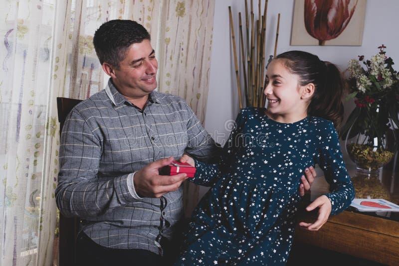 Muchacha feliz que da el regalo al padre sonriente el día de padre fotografía de archivo libre de regalías
