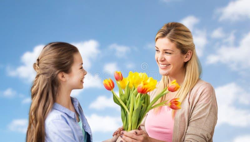 Muchacha feliz que da las flores a la madre sobre el cielo azul fotografía de archivo libre de regalías