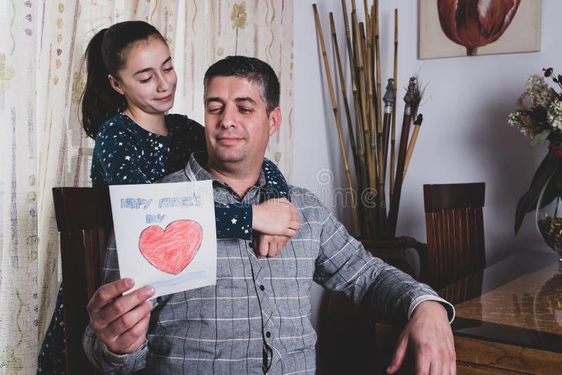 Muchacha feliz que distribuye la tarjeta de felicitación al padre sonriente el día de padre imagenes de archivo