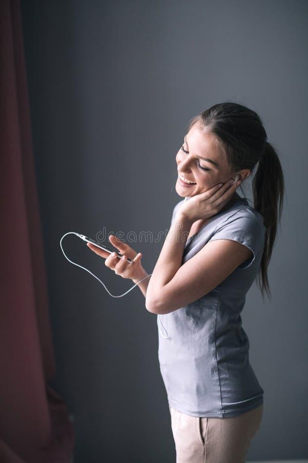Muchacha feliz que escucha la música del teléfono móvil en casa fotografía de archivo