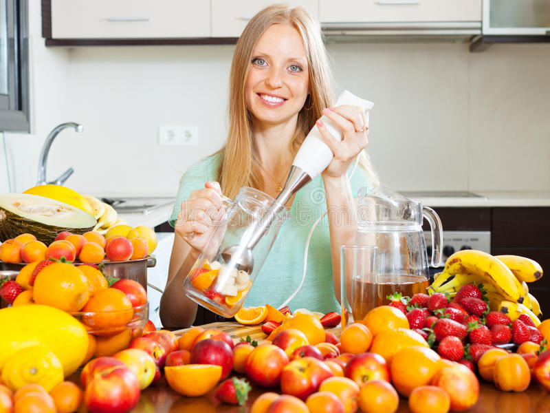 Muchacha feliz que hace la ensalada de fruta con la licuadora eléctrica foto de archivo
