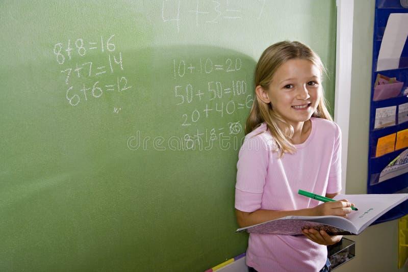 Muchacha feliz que hace matemáticas en la pizarra en clase fotografía de archivo libre de regalías