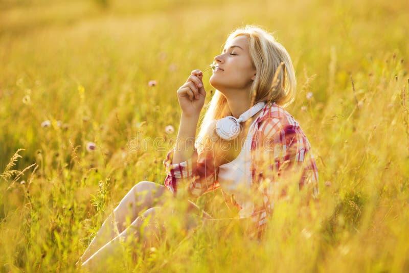 Muchacha feliz que huele una flor fotografía de archivo libre de regalías