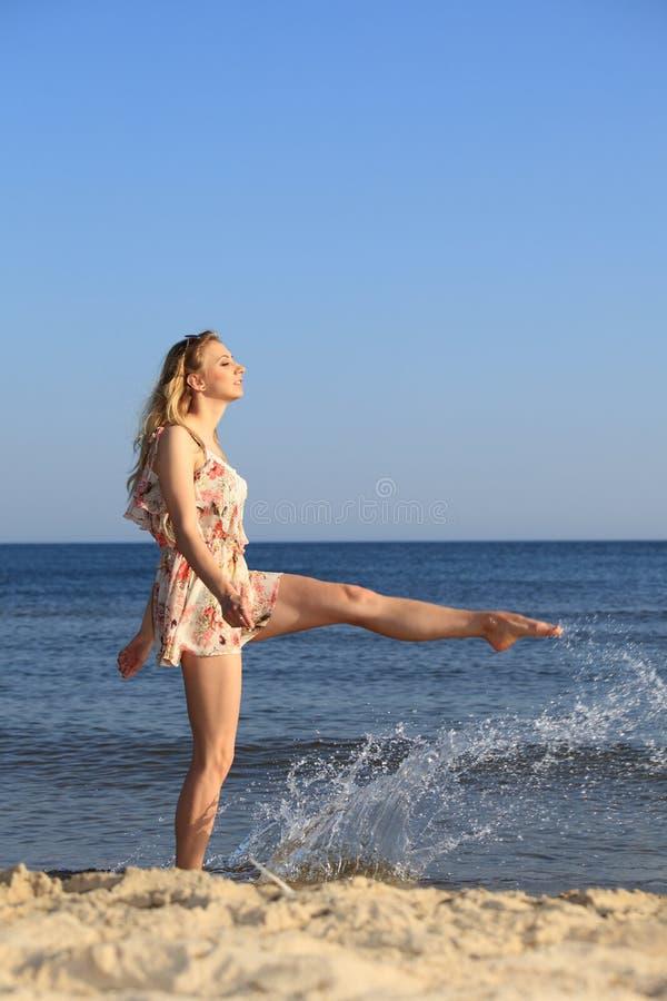 Muchacha feliz que juega con agua en la playa del verano imagen de archivo