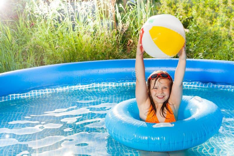 Muchacha feliz que juega con la bola del viento en la piscina imágenes de archivo libres de regalías