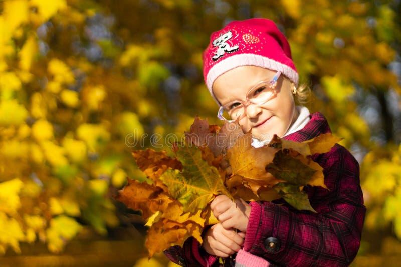 Muchacha feliz que juega con las hojas caidas en parque del otoño imagen de archivo