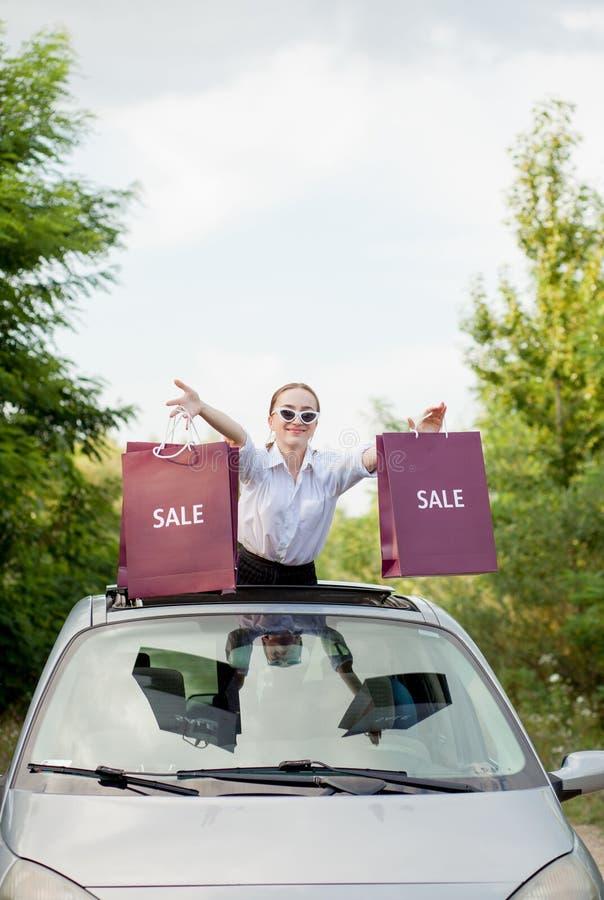Muchacha feliz que lleva a cabo los paquetes que hacen compras en la portilla del coche, el concepto de descuentos y hacer compra fotografía de archivo libre de regalías
