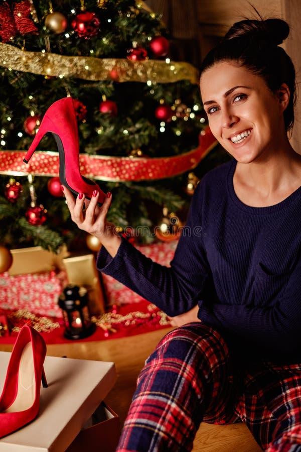 Muchacha feliz que lleva a cabo su presente delante del árbol de navidad fotos de archivo