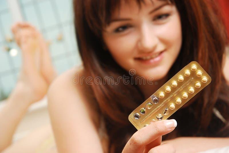 Muchacha feliz que mira sus píldoras anticonceptivas fotos de archivo libres de regalías