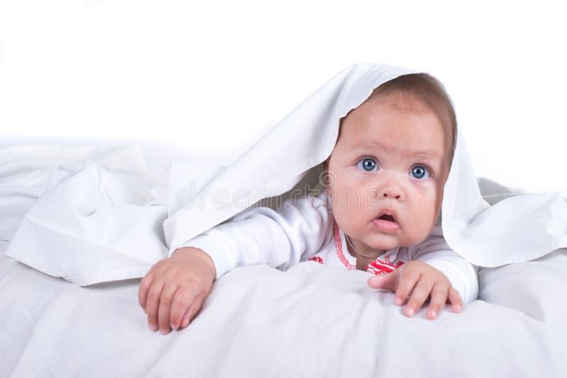 Muchacha feliz que oculta en cama debajo de una manta o de una sobrecama blanca Muchacha en la cama Niño en cama Aislado en el fo fotos de archivo libres de regalías