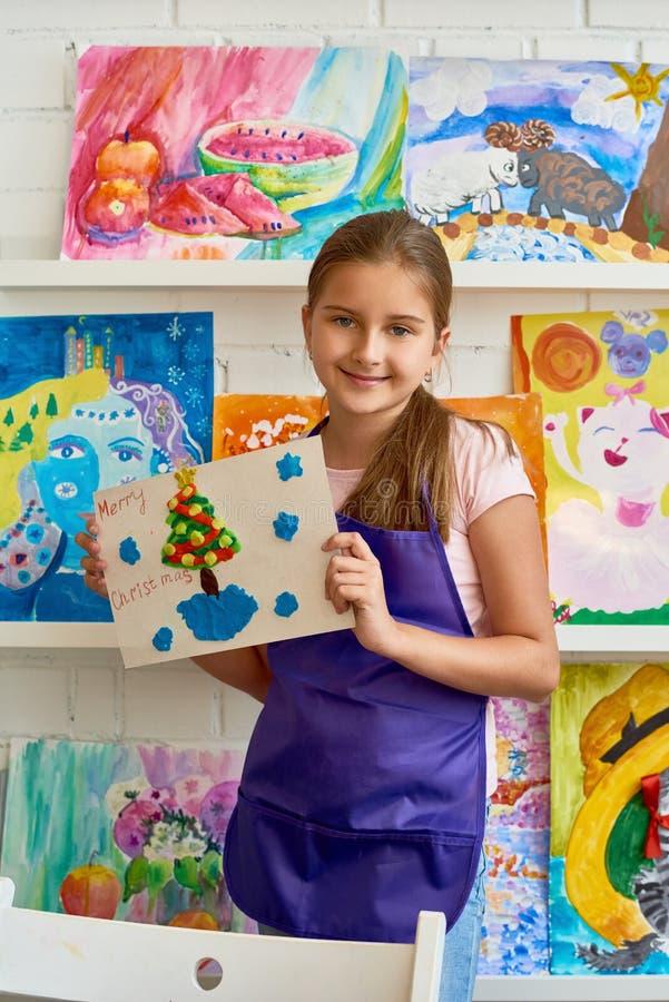 Muchacha feliz que presenta con la imagen de la Navidad foto de archivo