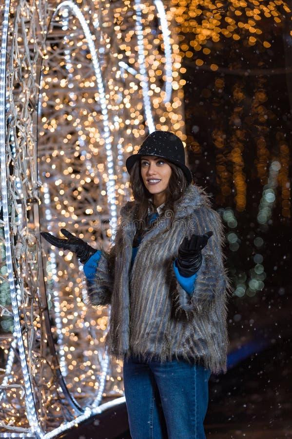 Muchacha feliz que presenta con las luces del invierno en el fondo foto de archivo libre de regalías