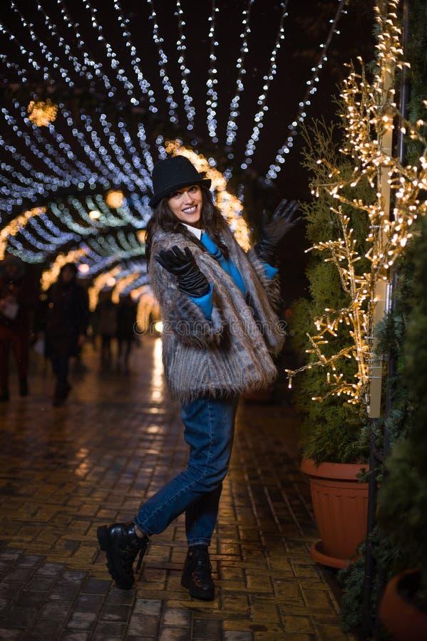 Muchacha feliz que presenta con las luces del invierno en el fondo imágenes de archivo libres de regalías