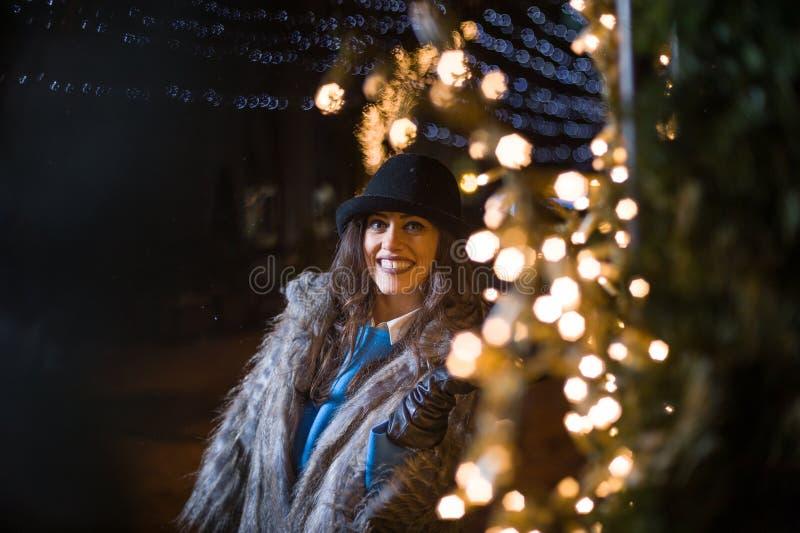 Muchacha feliz que presenta con las luces del invierno en el fondo imagenes de archivo